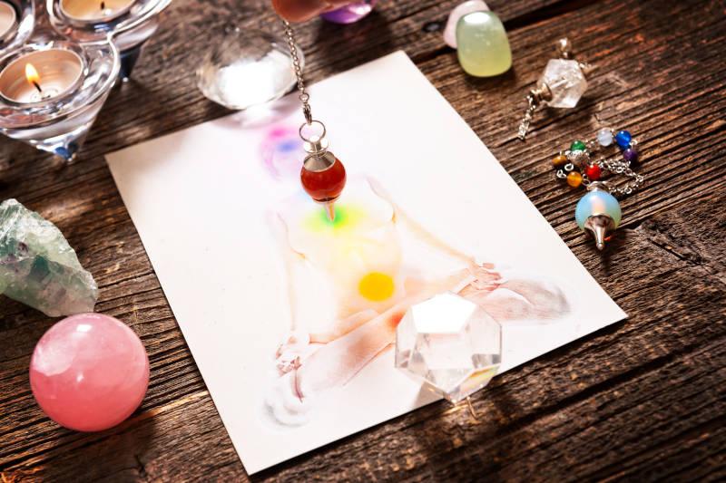 Cristalloterapia - Chakra illustrati con cristalli naturali e pendolo