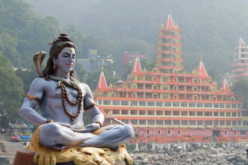 Statua di Shiva seduto in meditazione sulla riva del fiume Ganga a Rishikesh, Tempio di Tera Manzil